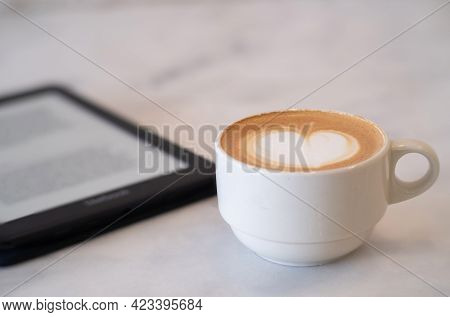 Close-up Of Hot Coffee Latte With Latte Art Milk Foam In Cup Or Mug With Ebook Reader Tablet On Desk