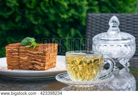 Crystal Cup With Mint Tea, Sugar Bowl And Medovik Cake On Table In Summer Cafe. Tea Drinking Concept