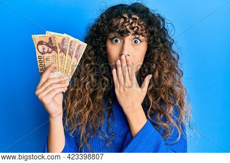 Young hispanic girl holding 5000 hungarian forint banknotes covering mouth with hand, shocked and afraid for mistake. surprised expression