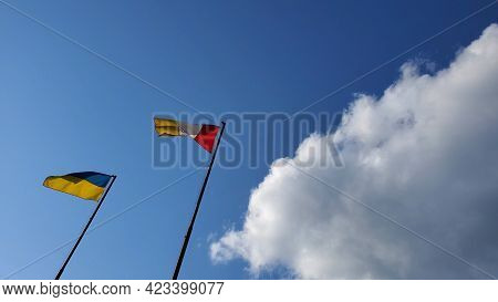 Ukrainian Flag And Odessa Flag Wave In Wind On Sky Background At Sunny Day. Yellow Blue Striped Flag
