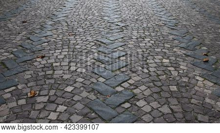 Ancient Stone Paving Road In Old Town. Cobblestone Pavement With Rectangular And Semicircular Stone