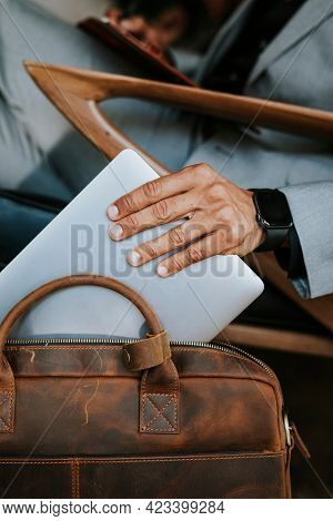 Man in a gray suit grabbing his laptop from a brown leather bag