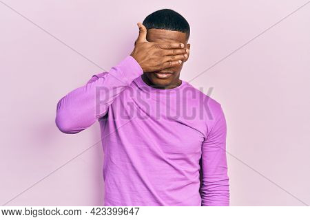 Young black man wearing casual pink sweater covering eyes with hand, looking serious and sad. sightless, hiding and rejection concept