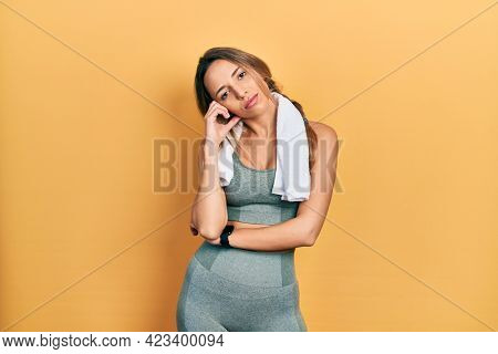 Beautiful hispanic woman wearing sportswear and towel thinking looking tired and bored with depression problems with crossed arms.