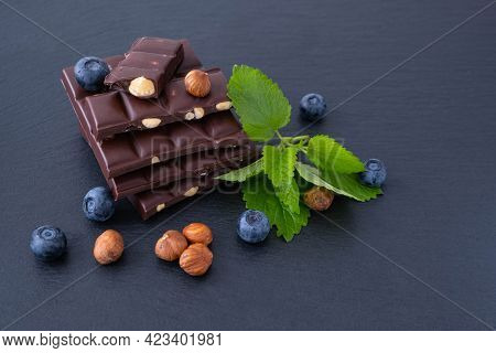 Chocolate Bars With Hazelnuts, Next To Mint, Blueberries And Hazelnuts, On A Black Background