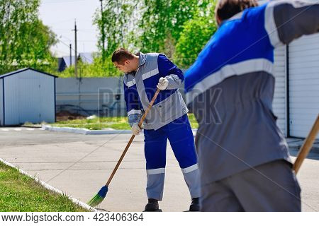 Two Men In Working Overalls On A Sunny Summer Day Sweep The Territory In The Open Air With Brooms. A