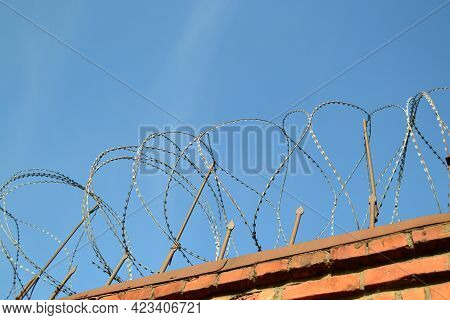 A Close-up Of Barbed Wire On An Old Brick Wall With A Blue Sky In The Background. The View From The