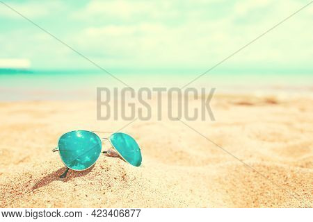 Sunglasses On The Beach. Summer Holidays At The Sea. Vacation On The Ocean. Reflection Of The Sky An