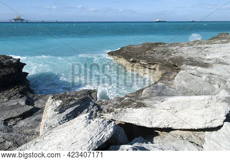 The View Of Grand Bahama Island Eroded Shore And Industrial Ships In A Background.