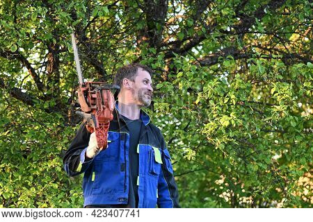 Strong, Confident Man Holds A Chainsaw In His Hands. A Woodcutter In Work Clothes With A Saw On Tree
