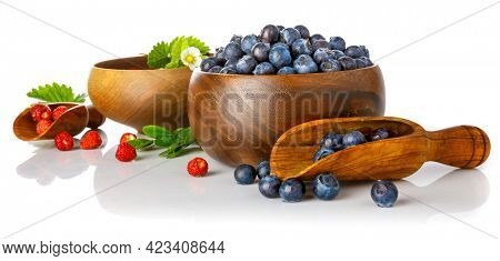 Berry blueberry and wild strawberry in wooden dish with green leaves and flower. Fruity still life. Healthy eating, isolated on white background.
