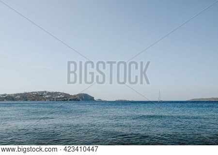 Turquoise Sea Waters Off The Coast Of Mykonos, Greece, On A Sunny Summer Day, Land And A Yacht In Th