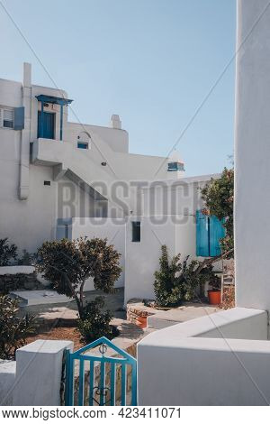 Exterior Of A Typical Mykonian White House With Blue Fence, Door And And Window Shutters In Mykonos,