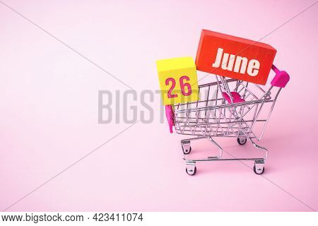 June 26th. Day 26 Of Month, Calendar Date. Close Up Toy Metal Shopping Cart With Red And Yellow Box