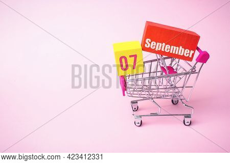 September 7th. Day 7 Of Month, Calendar Date. Close Up Toy Metal Shopping Cart With Red And Yellow B