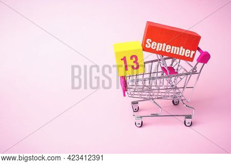September 13rd. Day 13 Of Month, Calendar Date. Close Up Toy Metal Shopping Cart With Red And Yellow