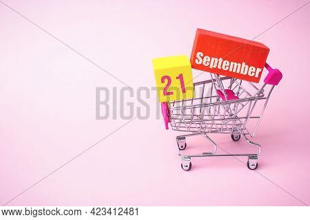September 21st . Day 21 Of Month, Calendar Date. Close Up Toy Metal Shopping Cart With Red And Yello