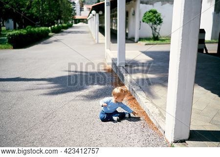 Little Girl Sits On The Road Near The Pavilion In The Park And Reaches For A Pebble