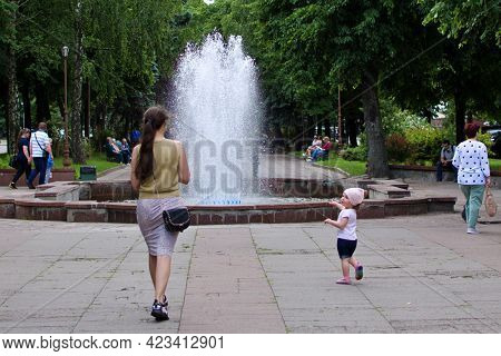 Young Woman With A Little Girl On Background Of Fountain In Green Park. Fountain Jets Rising Up. Ukr