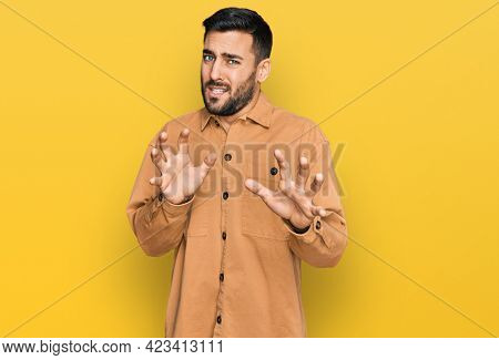 Young hispanic man wearing casual clothes disgusted expression, displeased and fearful doing disgust face because aversion reaction. with hands raised