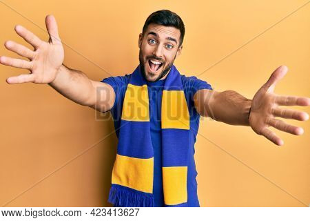 Young hispanic man football hooligan cheering game looking at the camera smiling with open arms for hug. cheerful expression embracing happiness.