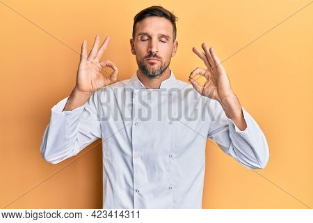 Handsome man with beard wearing professional cook uniform relax and smiling with eyes closed doing meditation gesture with fingers. yoga concept.
