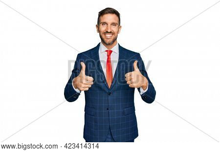 Handsome man with beard wearing business suit and tie success sign doing positive gesture with hand, thumbs up smiling and happy. cheerful expression and winner gesture.