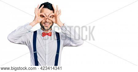 Hispanic man with beard wearing hipster look with bow tie and suspenders doing ok gesture like binoculars sticking tongue out, eyes looking through fingers. crazy expression.