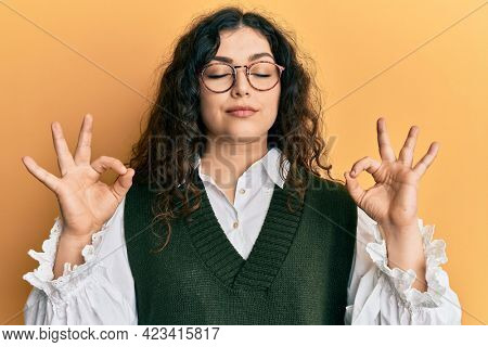 Young brunette woman with curly hair wearing casual clothes and glasses relax and smiling with eyes closed doing meditation gesture with fingers. yoga concept.