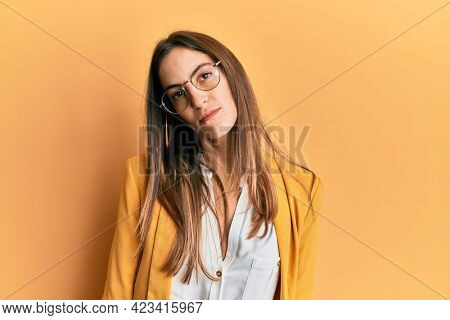 Young beautiful woman wearing business style and glasses looking sleepy and tired, exhausted for fatigue and hangover, lazy eyes in the morning.