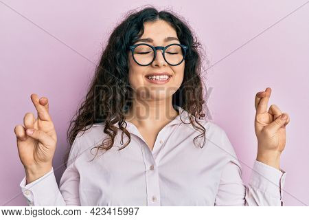 Young brunette woman with curly hair wearing casual clothes and glasses gesturing finger crossed smiling with hope and eyes closed. luck and superstitious concept.