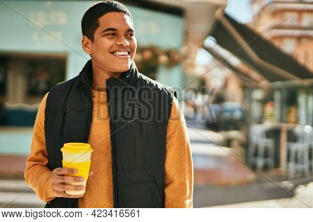 Young latin man smiling happy drinking coffee at the city