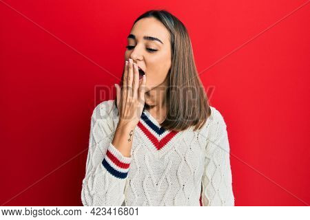 Young brunette girl wearing casual student sweater bored yawning tired covering mouth with hand. restless and sleepiness.