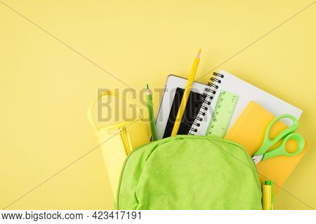 Overhead Photo Of Backpack Ruler Notepad Pen Pencil Tablet And Pencil-case Isolated On The Yellow Ba