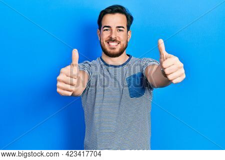 Handsome caucasian man with beard wearing casual striped t shirt approving doing positive gesture with hand, thumbs up smiling and happy for success. winner gesture.