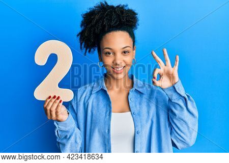 Young african american girl holding number two doing ok sign with fingers, smiling friendly gesturing excellent symbol