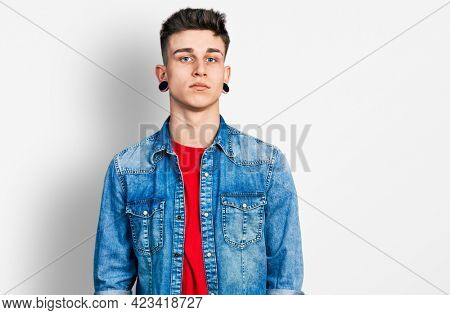 Young caucasian boy with ears dilation wearing casual denim jacket relaxed with serious expression on face. simple and natural looking at the camera.