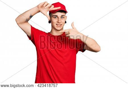 Young caucasian boy with ears dilation wearing delivery uniform and cap smiling making frame with hands and fingers with happy face. creativity and photography concept.
