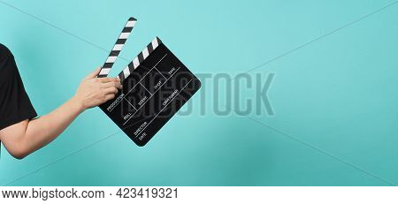 Hand Is Holding Black Clapper Board Or Movie Slate On Green Or Mint Or Tiffany Blue Background.