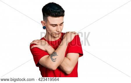 Young caucasian boy with ears dilation wearing casual red t shirt hugging oneself happy and positive, smiling confident. self love and self care