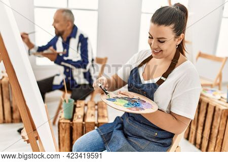 Young artist woman and senior painter man at art studio classroom painting on canvas, close up of woman pouring oil paint on artist palette
