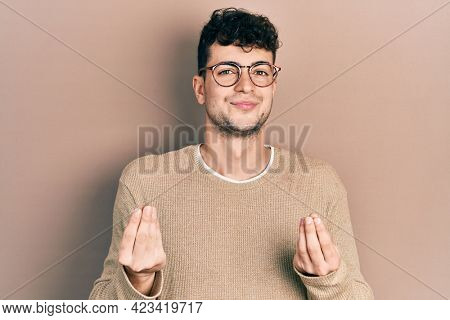 Young hispanic man wearing casual clothes and glasses doing money gesture with hands, asking for salary payment, millionaire business