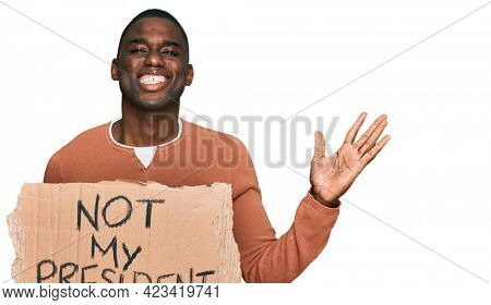 Young african american man holding not my president protest banner celebrating victory with happy smile and winner expression with raised hands