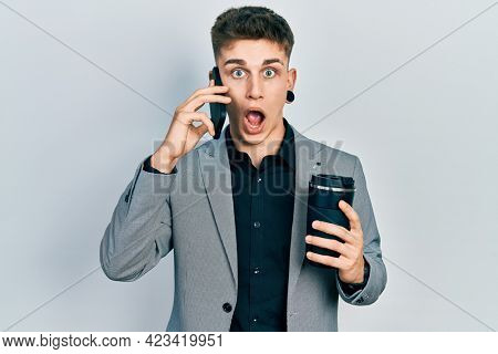 Young caucasian boy with ears dilation using smartphone and drinking a cup of coffee afraid and shocked with surprise and amazed expression, fear and excited face.