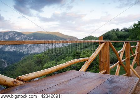 Panorama Of Wooden Table On Deck And Fence With Mountain Range Scenery