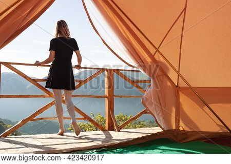 Rear View Of Blonde Caucasian Young Woman With Black Dress Watching The Mountains In The Morning On
