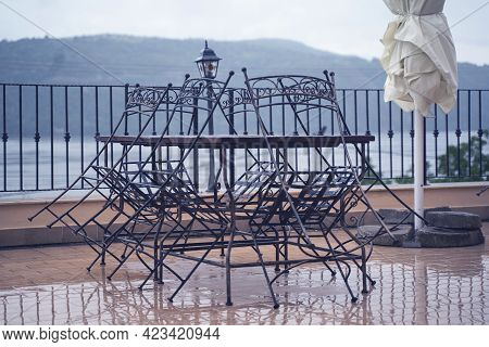 Closeup Detail Of Black Iron Metal Chairs Near Wooden Table With Rain Drops On Rainy Outdoor Restaur