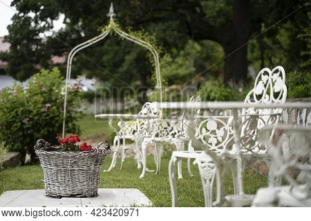 Empty Green Wedding Garden With Red Flowers In Wicker Basket And White Victorian Metal Decorative Ta