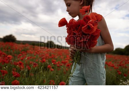 Side View Closeup Portrait Of Young Caucasian Girl With Light Blue Pants Holding A Bouquet Of Flower