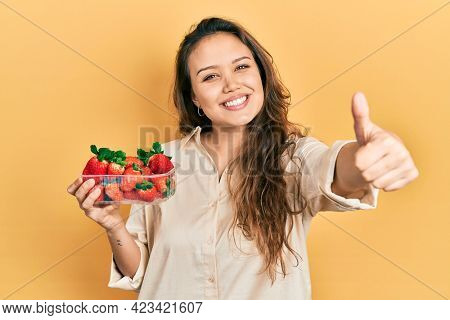 Young hispanic girl holding strawberries approving doing positive gesture with hand, thumbs up smiling and happy for success. winner gesture.